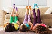 Three girls lying on floor with legs up