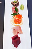 A Variety of Sashimi in a row with a Maple Leaf and Fresh Wasabi