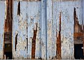 Verwitterte Holztür mit abgeblätterter blauer Farbe (Ausschnitt)