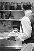 Waiter carrying plates in restaurant
