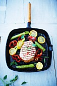 Smoked pork chop in a griddle pan with lemons and peppers