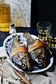 Two trout stuffed with prunes and chestnuts, wrapped in bacon