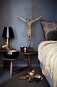 Holz Nachttisch mit mehreren, runden Ablagen, darauf Tischleuchte Bedside Gun und Jesusfigur neben Bett mit Fell Tagesdecke, auf Boden liegende Sportschuhe