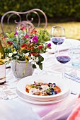 And Outdoor Table set for Dining with a Bowl of Mixed Shellfish in a Tomato Broth with Micro Greens