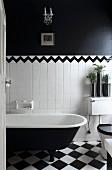 Blick durch offene Tür in schwarzweisses Bad - Vintage Badewanne auf Schachbrettmusterboden vor halbhoher, weisser Fliesenwand abgesetzt durch Bordüre von schwarzer Wandfläche