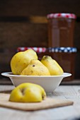 Fresh quinces in front of jam jars filled with quince jelly