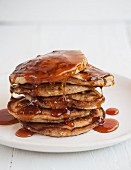 A stack of pancakes with orange syrup
