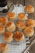Several scones on a wire rack in front of a jar of jam