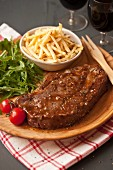 Beef steak with skinny fries, rocket and tomatoes