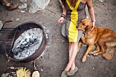 A Woman and Dog sitting by a Campfire Roasting Marshmallows