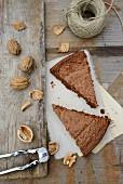 Zwei Stücke Schokoladen-Walnuss-Kuchen, Walnüsse, Nussknacker, Garnrolle