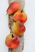 Four red pears on a piece of wood