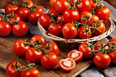 Fresh vine-ripened tomatoes, in a basket and on a chopping board
