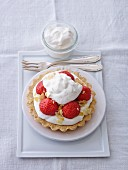 Strawberry tartlet with cream and flaked almonds