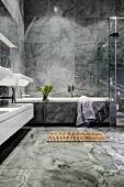 Luxuriöses Badezimmer mit grauen Marmorfliesen und einer Holzmatte vor der Badewanne
