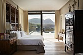 Helles Schlafzimmer mit antiken Holzmöbeln und mit herrlichem Blick auf die Landschaft durch eine raumhohe Glasfront