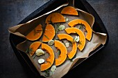 Slices of raw butternut squash with garlic and rosemary in a roasting tin