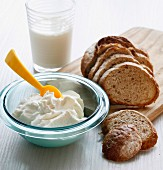 Quark in a glass bowl with bread and milk