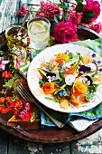 Colourful vegetable salad with radishes and edible flowers