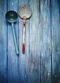 Alte Küchenutensilien (Kelle, Sieblöffel) auf blauem Holzuntergrund