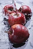 Rote Äpfel im Wasser mit Wasserstrahl