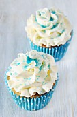 Two cupcakes topped with buttercream and blue sugar