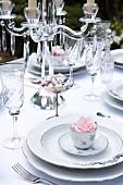 Festlich gedeckte Hochzeitstafel mit Porzellantellern, Kristallgläsern und Kerzenleuchter