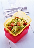 Potato salad with avocado and cherry tomatoes in a Tupperware container