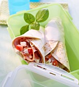 Wraps with ham, tomatoes and mozzarella, in a Tupperware container