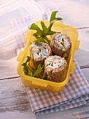 Packed lunch wraps with cheese and rocket in a Tupperware container