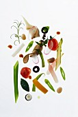 A still life of vegetables and herbs against a white background
