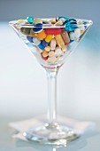 Lots of different tablets and pills in a cocktail glass