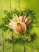 A peacock made from a sesame seed bun, ham, cheese and pickled gherkins