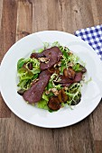Sliced saddle of venison on salad leaves with plums and walnuts