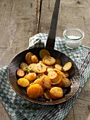 Fried potatoes in a pan on a tea towel
