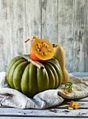 Half a Hokkaido squash on a green winter squash by a wooden wall