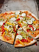 Vegetable pizza with courgette and peppers, one slice cut