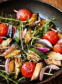 Vegetable skewers with cherry tomatoes, courgette and onions in a frying pan