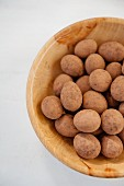 Cocoa & chocolate treats in a wooden bowl (view from above)