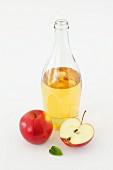 A bottle of cider vinegar and fresh apples