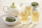 Three glasses of wild garlic tea, a teapot and tea leaves