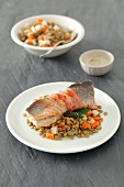 Trout wrapped in bacon on a lentil and carrot salad
