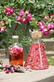 Rose petals being steeped in vinegar and a bottle of rose vinegar