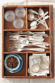 An old drawer with forks, spoons, napkin rings and cloves