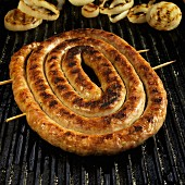 Coil of Italian Sausage on Grill with Onions