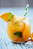Orange juice with ice cubes and orange slices