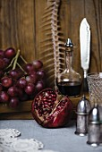 A still life featuring a fish skeleton, pomegranate, grapes and red wine