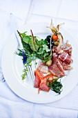 charcuterie plate, salami, prosciutto, smoked salmon, green salad