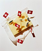 A chunk of cheese decorated with Swiss flags and miniature cow figures