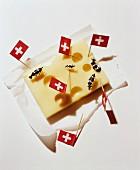 Stück Käse dekoriert mit Schweizer Fähnchen & Kuhfiguren